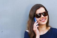 Mujer alegre que habla en el teléfono en el equipo casual de la calle Imagen de archivo libre de regalías