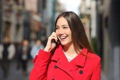 Mujer alegre que habla en el teléfono en la calle Imagen de archivo