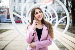 Mujer alegre que habla en el teléfono en la calle que lleva una chaqueta rosada Foto de archivo libre de regalías