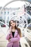 Mujer alegre que habla en el teléfono en la calle que lleva una chaqueta rosada Fotografía de archivo libre de regalías