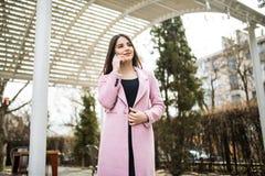 Mujer alegre que habla en el teléfono en la calle que lleva una chaqueta rosada de la capa Fotos de archivo libres de regalías