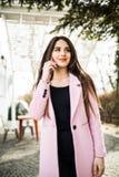 Mujer alegre que habla en el teléfono en la calle que lleva una chaqueta rosada de la capa Fotografía de archivo libre de regalías