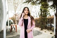 Mujer alegre que habla en el teléfono en la calle que lleva una chaqueta rosada de la capa Foto de archivo libre de regalías