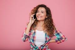 Mujer alegre que habla en el teléfono y risa aislada sobre rosa Imágenes de archivo libres de regalías