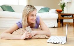 Mujer alegre que hace compras en línea mintiendo en el suelo Imagenes de archivo