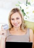 Mujer alegre que hace compras en línea mintiendo en un sofá Imagen de archivo