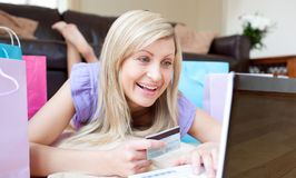 Mujer alegre que hace compras en línea mintiendo en el suelo Fotografía de archivo libre de regalías