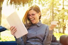 Mujer alegre que hace una pausa su nuevo coche que busca trabajo con el ordenador del cojín en un parque urbano del verano imágenes de archivo libres de regalías