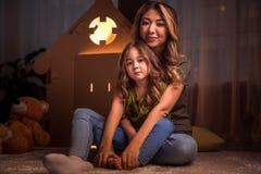 Mujer alegre que juega con su niño en el apartamento Imagen de archivo libre de regalías