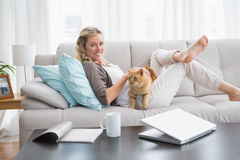 Mujer alegre que miente en el sofá que abraza un gato del jengibre Imagenes de archivo