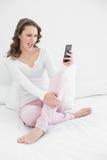 Mujer alegre que mira el teléfono móvil en cama Imágenes de archivo libres de regalías