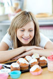 Mujer alegre que mira las tortas en la cocina Imagenes de archivo