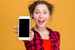 Mujer alegre que muestra la pantalla en blanco del smartphone Imagenes de archivo
