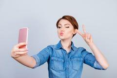 Mujer alegre que muestra la v-muestra mientras que toma el selfie en su smartp Imagenes de archivo