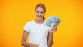 Mujer alegre que muestra los pulgares encima de llevar a cabo dólares a disposición, trabajo bien pagado, beneficio almacen de video