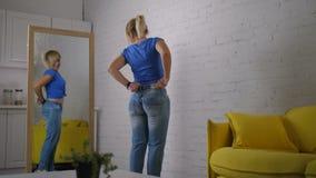 Mujer alegre que muestra su logro de la pérdida de peso metrajes