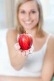 Mujer alegre que muestra una manzana Imágenes de archivo libres de regalías