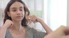 Mujer alegre que pone los pendientes al oído que mira en espejo del cuarto de baño en casa metrajes