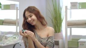 Mujer alegre que rocía el aerosol oral para la respiración fresca en boca en sitio del baño almacen de metraje de vídeo