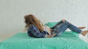 Mujer alegre que salta en cama metrajes