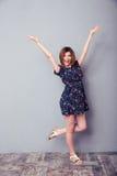 Mujer alegre que se coloca con las manos aumentadas para arriba Imagenes de archivo
