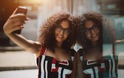 Mujer alegre que se fotografía que usa el teléfono móvil imagenes de archivo