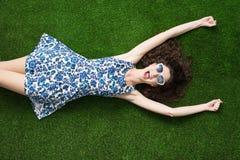 Mujer alegre que se relaja en la hierba Fotos de archivo