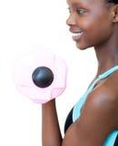 Mujer alegre que se resuelve con pesa de gimnasia Fotos de archivo libres de regalías