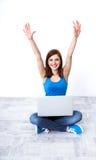 Mujer alegre que se sienta en el piso con el ordenador portátil Fotografía de archivo