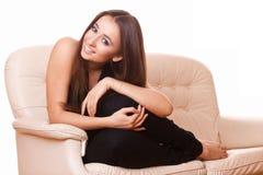 Mujer alegre que se sienta en el sofá Fotografía de archivo