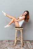 Mujer alegre que se sienta en la silla con las piernas aumentadas Foto de archivo libre de regalías
