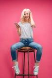 Mujer alegre que se sienta en la silla y la música que escucha Imagenes de archivo