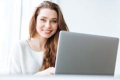 Mujer alegre que se sienta en la tabla con el ordenador portátil Fotografía de archivo