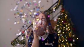 Mujer alegre que sopla confeti colorido de la mano almacen de video