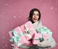 Mujer alegre que sostiene muchas cajas con los regalos en un fondo rosado fotografía de archivo libre de regalías