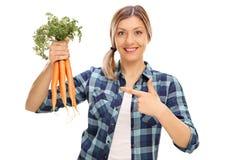 Mujer alegre que sostiene un manojo de zanahorias Fotos de archivo libres de regalías