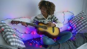 Mujer alegre que toca la guitarra en luces de la guirnalda almacen de metraje de vídeo