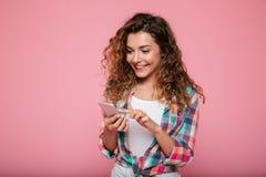Mujer alegre que usa el smartphone aislado sobre rosa Fotografía de archivo