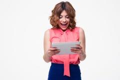 Mujer alegre que usa la tableta Foto de archivo libre de regalías