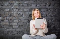 Mujer alegre que usa la tableta digital portátil Foto de archivo libre de regalías