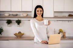 Mujer alegre que usa su ordenador portátil en la cocina fotografía de archivo libre de regalías