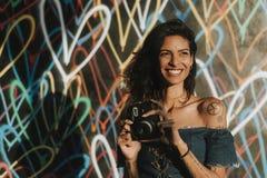 Mujer alegre que usa una cámara instantánea fotos de archivo