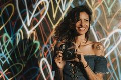 Mujer alegre que usa una cámara instantánea foto de archivo