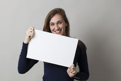 Mujer alegre 20s que goza haciendo un anuncio en la exhibición de un parte movible en blanco Fotografía de archivo