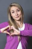 Mujer alegre 20s que muestra forma del corazón con las manos Imagenes de archivo