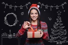 Mujer alegre sonriente que sostiene la caja con un presente Imágenes de archivo libres de regalías