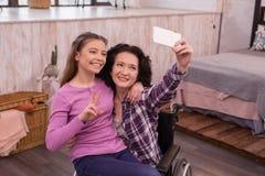 Mujer alegre y muchacha lisiadas que toman el selfie Imagen de archivo libre de regalías