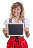 Mujer alemana en un dirndl bávaro tradicional con el tablero de tiza Imagen de archivo libre de regalías
