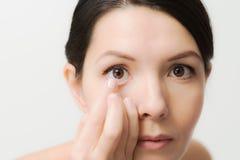Mujer alrededor para colocar una lente de contacto en su ojo fotografía de archivo libre de regalías
