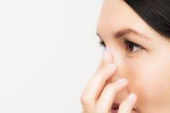 Mujer alrededor para colocar una lente de contacto en su ojo fotos de archivo libres de regalías